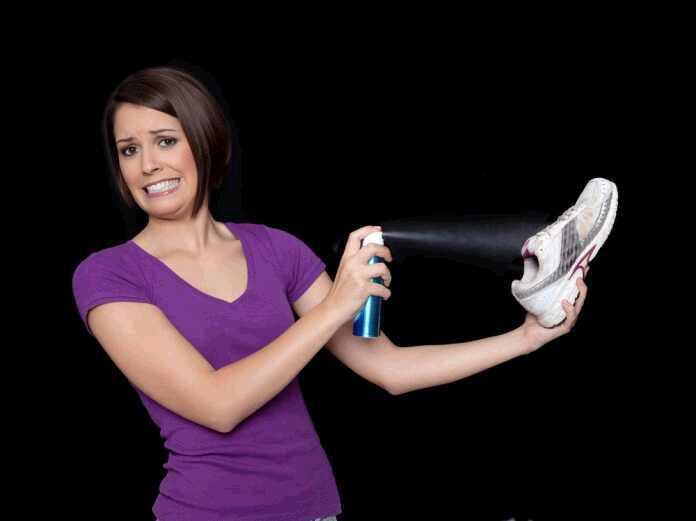woman spraying shoe